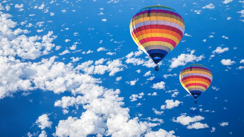 Colourful-hot-air-balloon-in sky-with-clouds-over-barcelona
