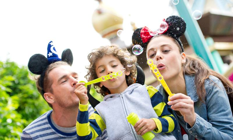 Man, lady and child blowing bubbles at Disneyland Paris