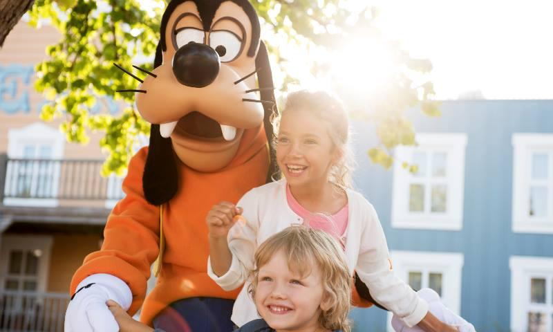 Two children standing with Goofy at Disneyland Paris