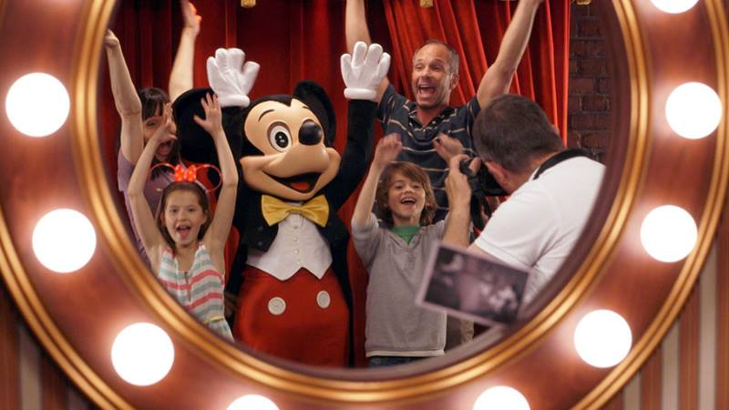 Family with Mickey Mouse holding up hands in a mirror at Disneyland Paris