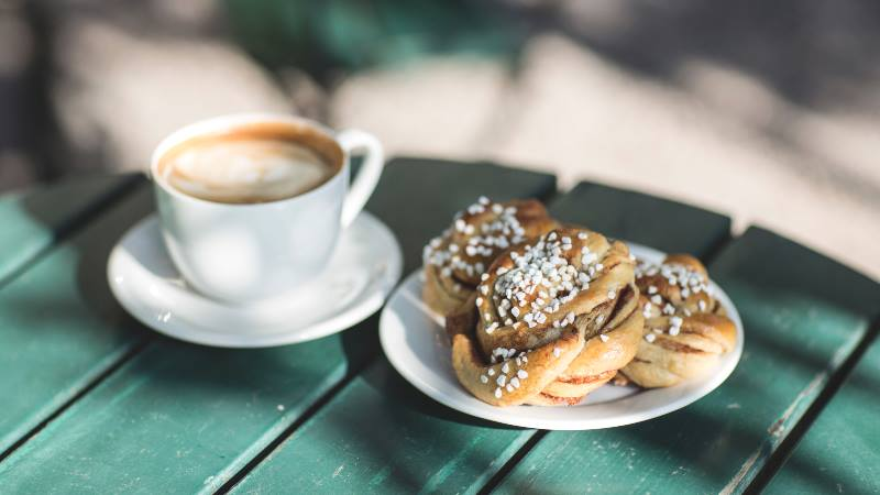 Coffee-and-cinnamon-bun-on-a-green-wooden-table-during-Fika