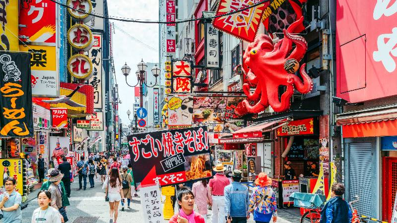 People-walking-through-busy-Osaka-street-with-many-food-signs-on-buildings-at-the-Rugby-World-Cup
