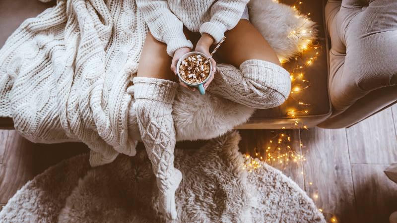 Lady-sitting-on-a-sofa-wearing-long-woollen-socks-hygge-style
