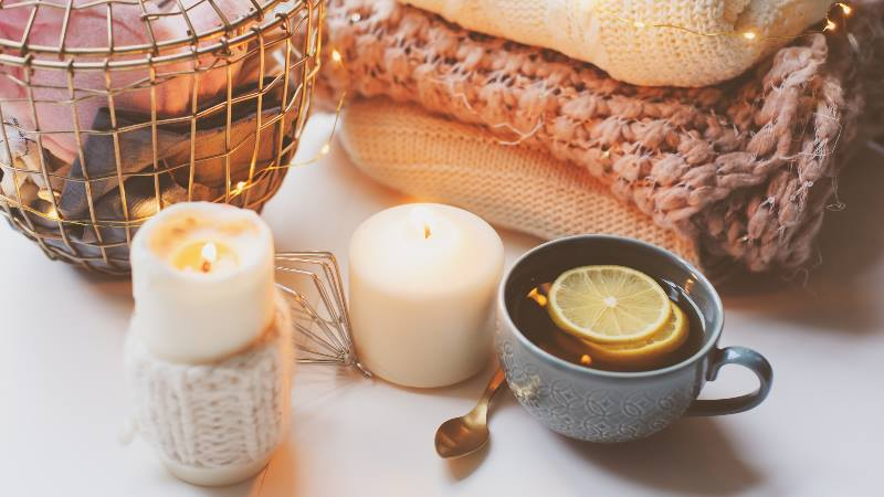 Hygge-concept-candles-drink-and-woollen-blankets