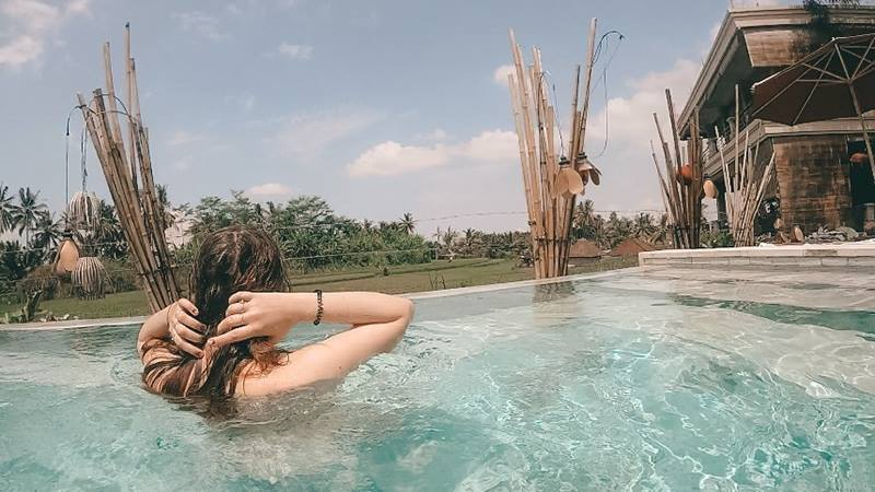 Female-brushing-her-hair-back-in-swimming-pool-on-a-travelling-solo-trip