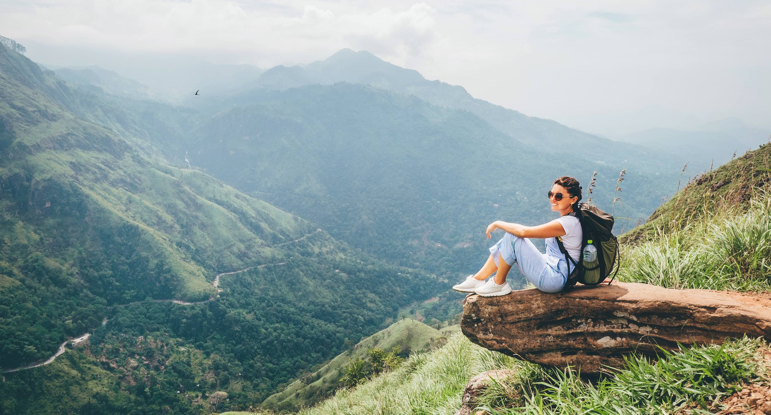 Lady-sitting-on-a-rock-looking-at-the-view-travelling-solo