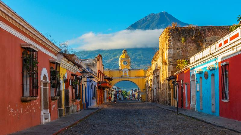 Street-scene-with-road-and-colourful-houses-A-volcano-in-the-background-in-Central-America