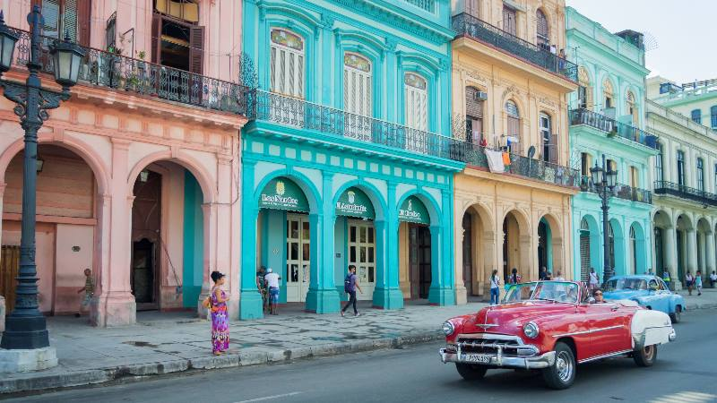 Street-scene-in-Havana-Central-America-Old-style-car-driving-down-a-colourful-street