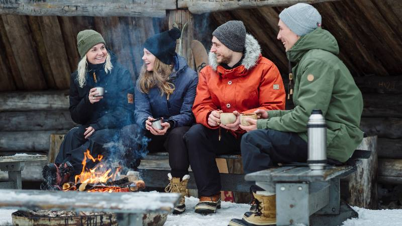 Group-of-people-sitting-around-keeping-warm-in-a-Nordic-winter
