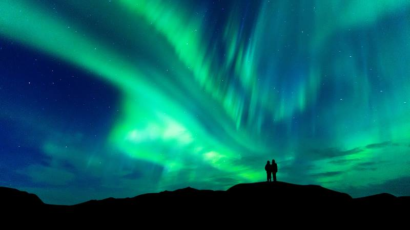 Two-people-watching-the-Northern-Lights-in-the-Winter