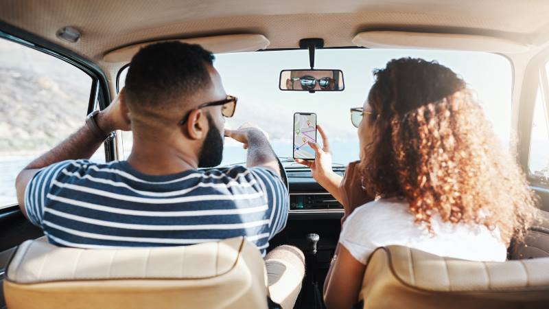 Two-people-in-a-car-searching-directions-on-the-phone-travel-apps-2020
