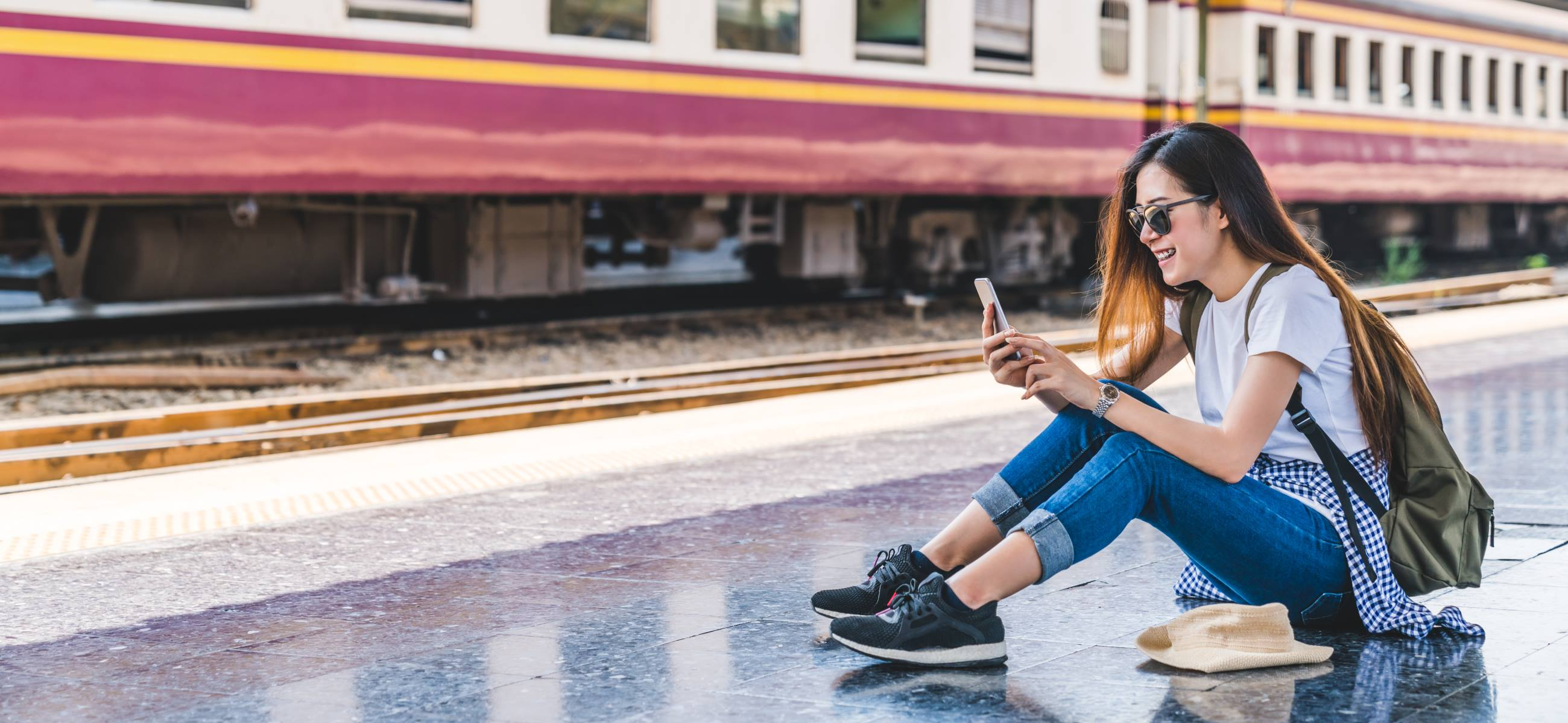 Asian-tourist-at-train-station-using-smartphone-map-social-media-check-in-or-buy-ticket-booking-Modern-travel-app-technology