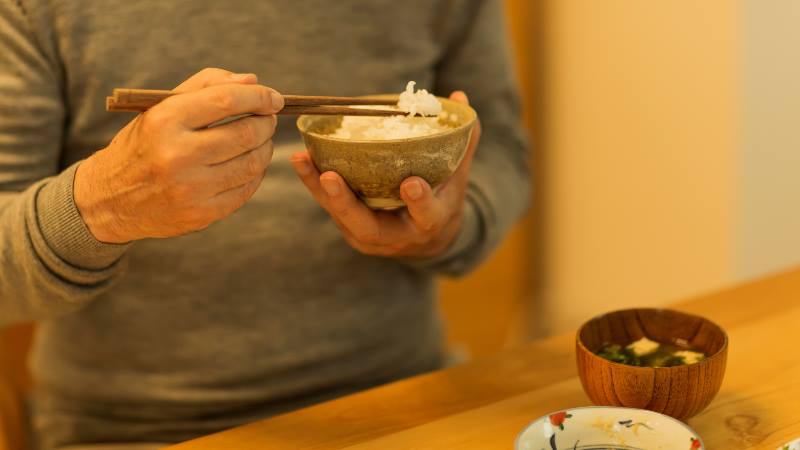 Man-holding-chopsticks-and-a-bowl-of-rice