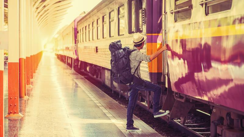 Man-climbing-aboard-a-train-Sustainable-travel-train