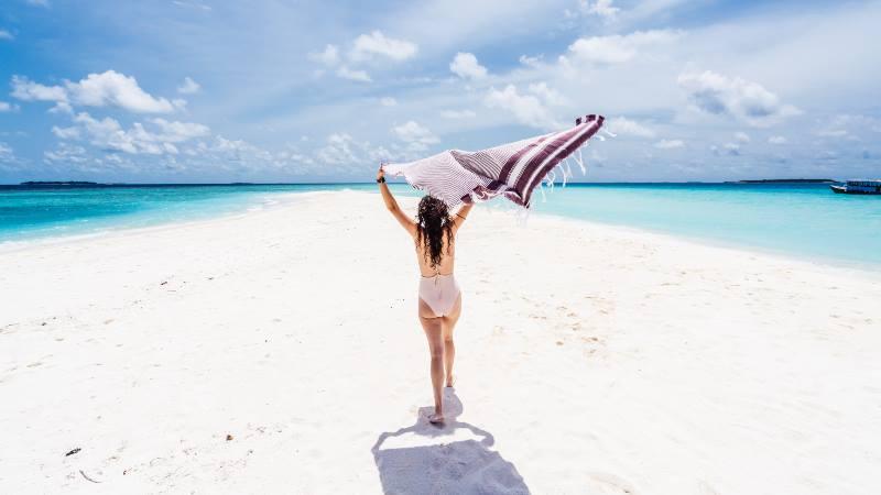 woman-waving-a-towel-on-sandy-beach