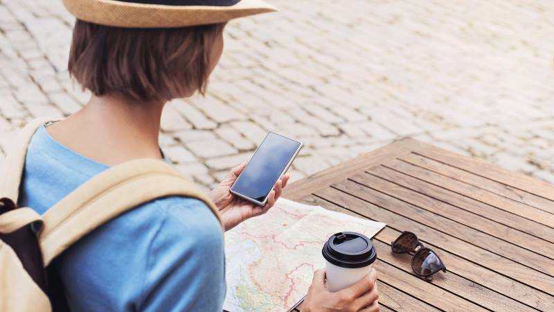Lady-with-coffee-sitting-at-a-cafe-table-with-map-and-phone-out