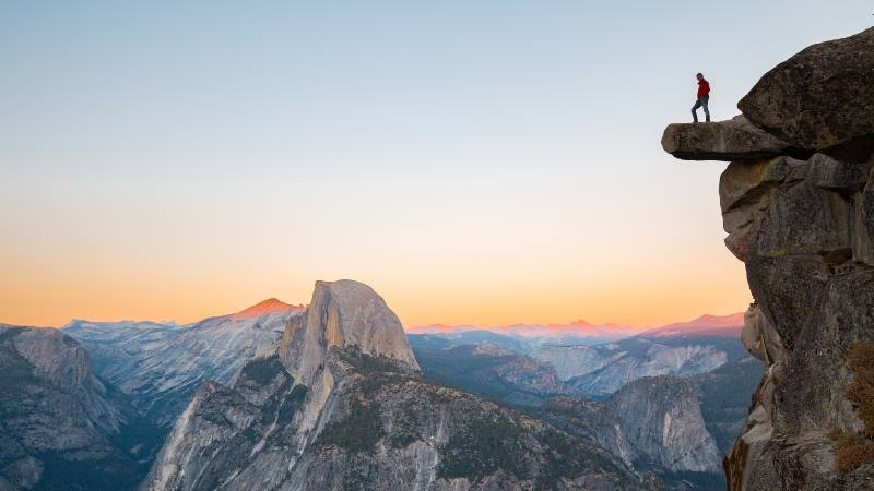 A-fearless-hiker-is-standing-on-an-overhanging-rock-enjoying-the-view-towards-famous-Half-Dome-at-Glacier-Point-overlook-in-beautiful-evening-twilight-Yosemite-National-Park-California-USA