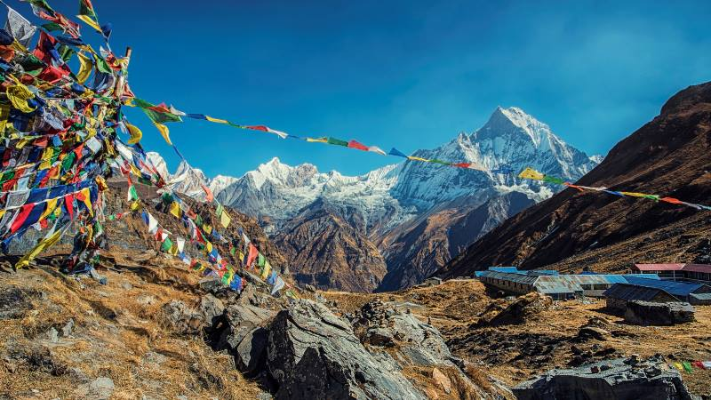 View-of-the-Annapurna-base-camp-with-flags-flying-in-the-foreground-mountains-to-climb
