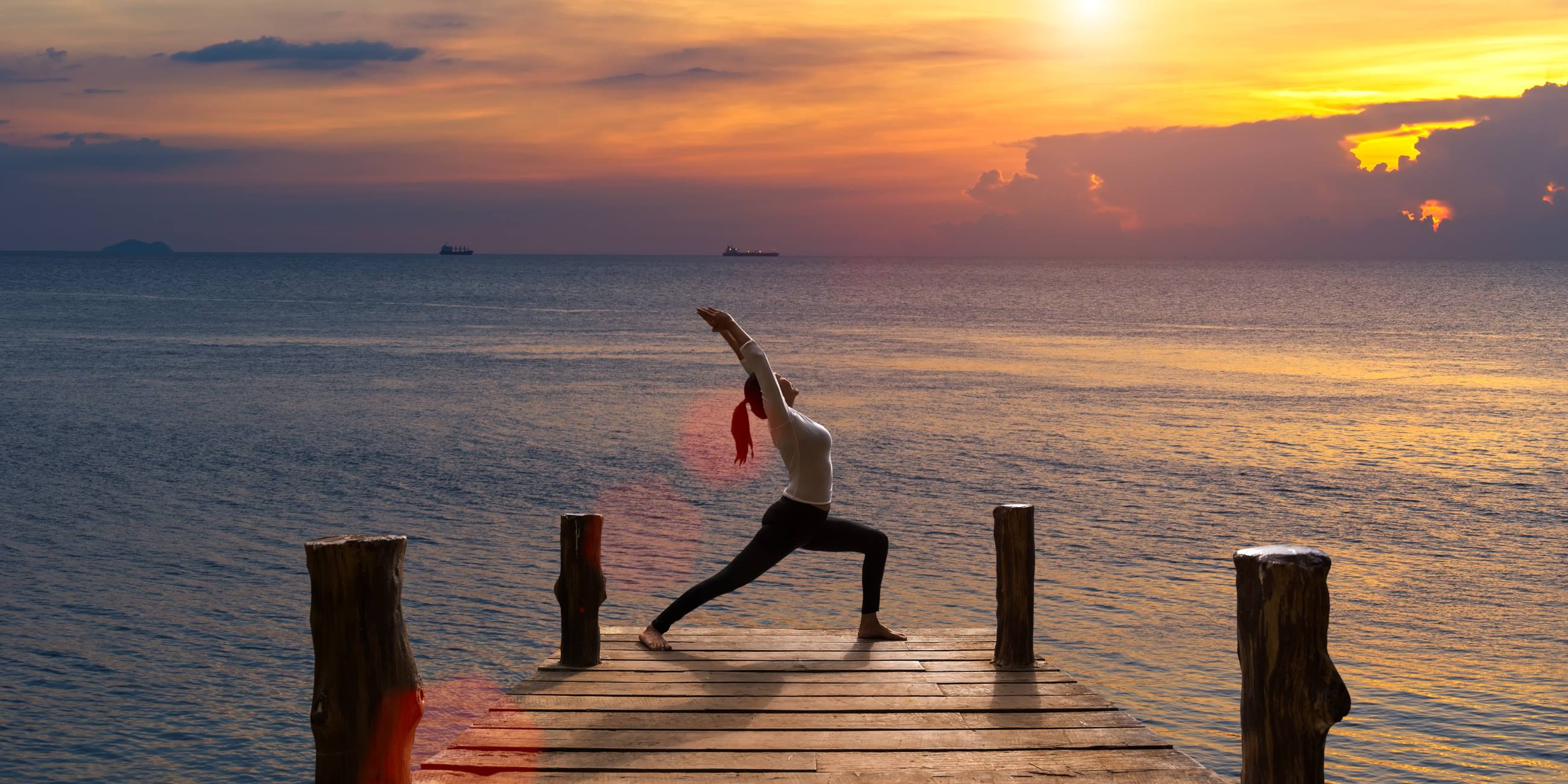 Meditation-girl-on-the-sea-during-sunset-on-the-wood-the-bridge-Yoga-silhouette-Fitness-and-healthy-lifestyle-mental-health