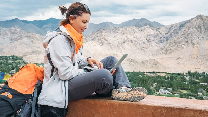 Backpacker-with-laptop-sits-on-the-top-view-point-under-mountain-settlement-mental-health