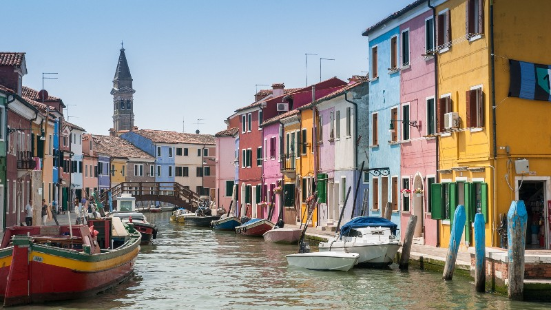 View of a canal heading into Murano and Burano with colourful buildings and boats near Venice