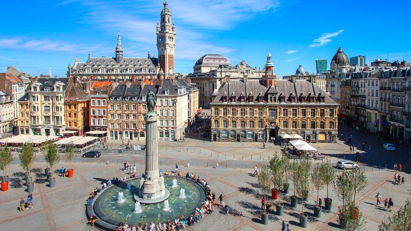 The main square in Lille. Fountain in the foreground and old buildings in the background